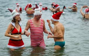"""Members of ice swimming club """"Berliner Seehunde"""" (Berlin Seals) take a dip in the Orankesee lake in Berlin as part of their traditional Christmas ice swimming session, in Berlin"""