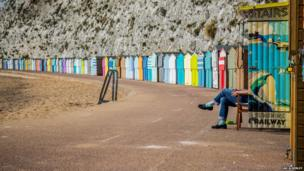 Beach huts and one person's legs
