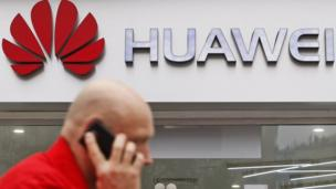Man strutts up in front of a Huawei sign