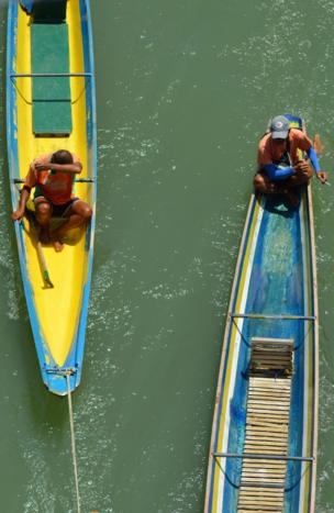 Two men sit in brightly painted canoe boats