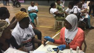 Woman wey dey check her blood sugar with medical volunteer