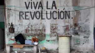 Man sleeping below words Viva La Revolucion on a wall.