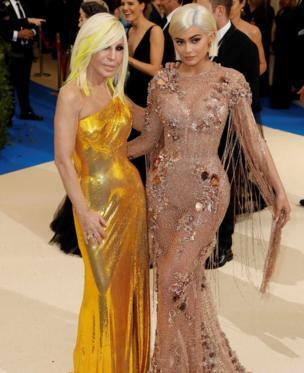 Kylie Jenner (iburyo) yifotozanya na Donatella Versace. Nk'uko ushobora kuba wabihishuye, Kylie yambaye- Versace.