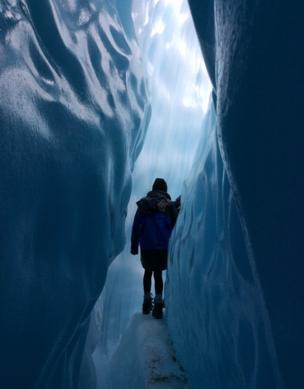 A girl walks through a glacier