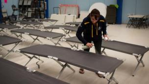 Wendy Tremblay, resident of Conklin, Alta., prepares cots for residents of Fort McMurray