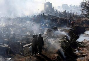 Pedagang dan polisi anti huru hara di lokasi kebakaran di pasar Gikomba di pusat Nairobi, Kenya.