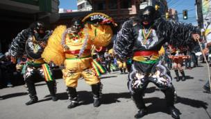 Participants wearing masks parade down the streets of La Paz