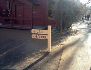 A signpost points left towards a jail and a school