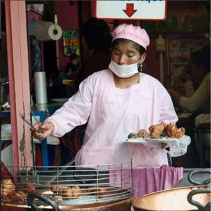 Mujer con tapabocas saca un chicharrón de una fritadora