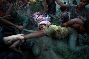 مصورون يساعدون امرأة من أقلية الروهينجا المسلمة على الخروج من نهر ناف، بعد رحلة العبور الشاقة من ميانمار إلى بنغلاديش