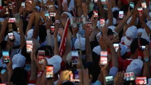 Mitingin katılımcıları cep telefonlarıyla sık sık fotoğraf çekti.