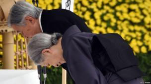 Emperor Akihito (L) and Empress Michiko (R) bow before the altar during the annual memorial service for war victims in Tokyo on 15 August 2015