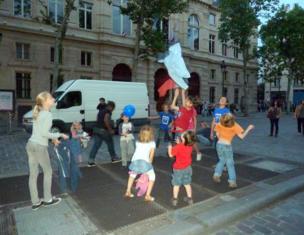 Niños jugando con sus chaquetas en una calle de París.