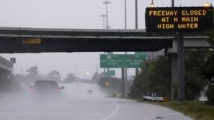 A pick-up truck passes a warning sign on southbound Interstate 45 north of Houston, TX, as heavy rains from the remnants of Hurricane Harvey continue to flood many areas of the city (27 August 2017)