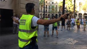 Local policeman tells tourists and residents to move away from the Ramblas