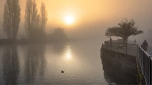 The sun breaking through the fog over the Thames in Abingdon along Wilsham Road