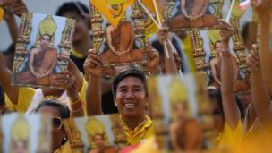 People hold portraits of the King as they wait for him and Queen Suthida to appear
