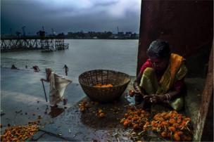 A woman squats down in Kolkata
