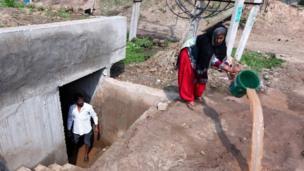 د هند تر کنټرول لاندې کشمیر کې یوه ځايي ښځه له هغه خندقه اوبه بهر ته باسي چې د جګړې په صورت کې د پناه ځای په توګه استعمالېږي.