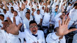 Men raise their hands and cry at an event held in Guadalajara by the Light of the World church.