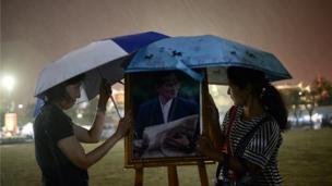 ผู้หญิงกางร่มบังฝนพระบรมฉายาลักษณ์