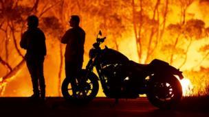 Moradores do lago Tabourie, cerca de 320 quilômetros ao sul de Sydney, na Austrália, observam as chamas devorarem uma floresta.