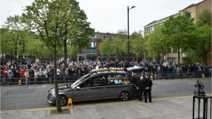 The funeral hearse arrives outside St. Anne's Cathedral in front of crowds of mourners.