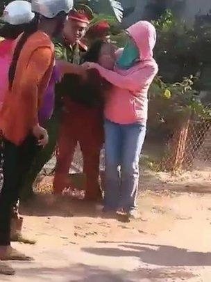 Hai cảnh sát và một phụ nữ đeo khẩu trang lôi kéo một người dân trong một clip