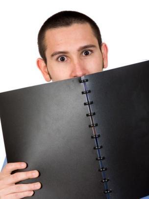 Hombre que oculta el rostro detrás de un cuaderno