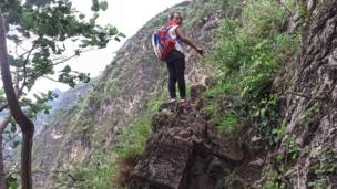 A girl of Atuler Village looks back during climbing a cliff on her way home in Zhaojue county in southwest China's Sichuan province on May 14, 2016 in Zhaojue, China.