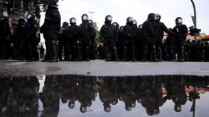Riot police are reflected in water on July 7, 2017 in Hamburg, northern Germany,