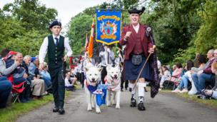 A man and a boy wearing Scottish tartan outfit are accompanied by two dogs as they lead