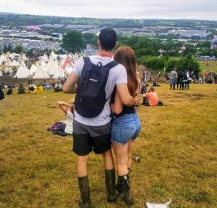 A couple hold each other as they look over Glastonbury festival