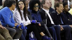 Singer Prince, in sunglasses, smiles as he watches an NBA basketball game between the Golden State Warriors and the Oklahoma City Thunder on Thursday, March 3, 2016, in Oakland, California