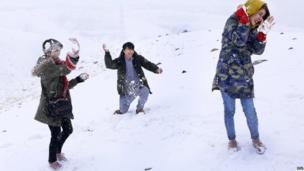 अफ़ग़ानिस्तान की राजधानी काबुल के पहाड़ी इलाके इन दिनों बर्फ़ की चादर से ढके हुए हैं, ऐसे में एक अफ़ग़ान युवक और दो युवतियां साल की पहली बर्फ़बारी का मज़ा लेते हुए.