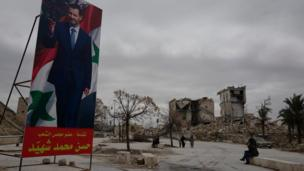 A brightly-coloured poster of President Assad stands in front of ruined buildings in Aleppo