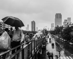 Rain pours on the city of Mumbai , people are getting wet as they use the over pass