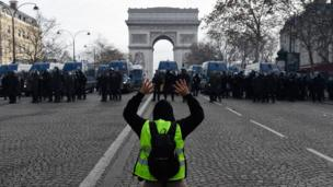 A protester kneels in front of police officers in Paris