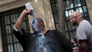 A man douses himself with a liquid, most likely milk of magnesium, to cope with the effects of pepper spray