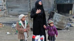 หญิงซีเรียคนหนึ่งเดินทางมาถึงย่านฟาร์ดอสพร้อมลูก ๆ