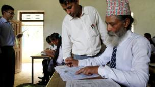 A teacher helps Durga Kami to fill an examination registration form