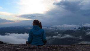 Mujer sentada en una cumbre