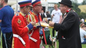 Bands men and member of Royal Black eating in field at Scarva, Craigavon, 13 July 2017