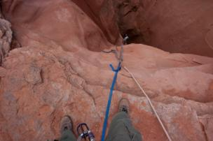 A view on a person rock-climbing a canyon.