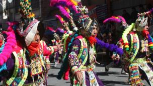 Richly adorned dancers parade through the streets of La Paz