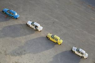 A queue of differently coloured taxis