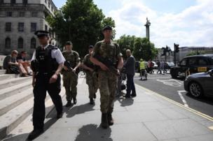 Armed soldiers walk with a police officer near Trafalgar Square on May 24, 2017