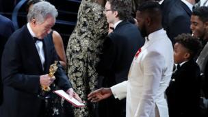 तारेल एल्विन मैक्रेनी को अवार्ड कार्ड दिखाते वॉरेन बेट्टी