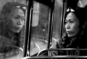 A woman stares out of the window of a bus