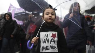 """Niña con paraguas con chaleco """"ni una menos"""""""